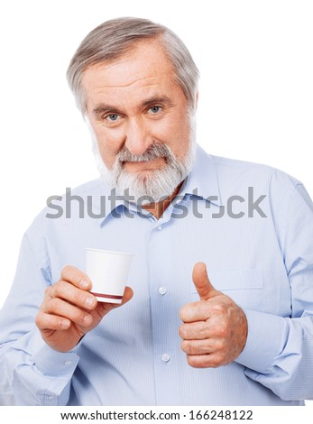 Portrait of smart old man drinking cup of coffee and showing sign OK - stock photo
