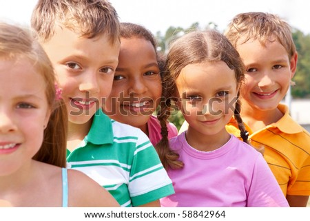 Portrait of smart preschoolers standing in row and looking at camera - stock photo