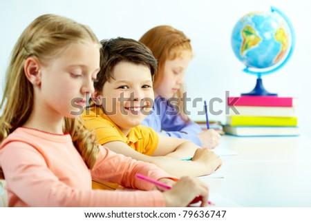 Portrait of smart schoolboy looking at camera between girls - stock photo