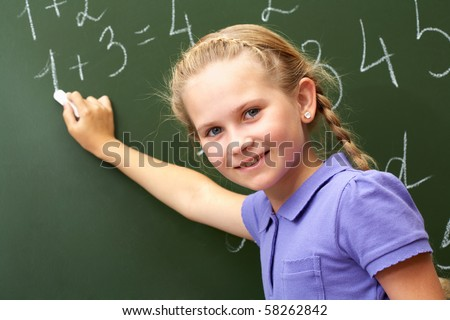Portrait of smart schoolchild by the blackboard looking at camera - stock photo