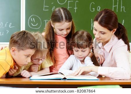 Portrait of smart schoolchildren and their teacher reading book in classroom - stock photo