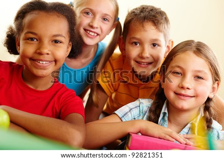 Portrait of smart schoolchildren looking at camera in classroom