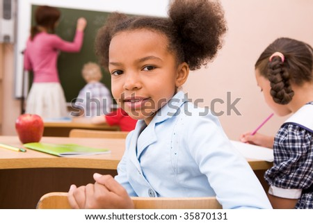Portrait of smart schoolgirl looking at camera during lesson