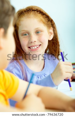 Portrait of smart schoolgirl looking at classmate at drawing lesson - stock photo