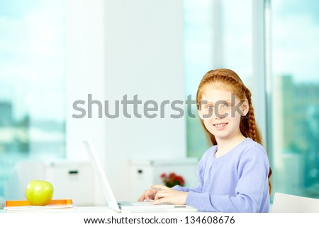 Portrait of smart schoolgirl sitting in classroom and typing - stock photo