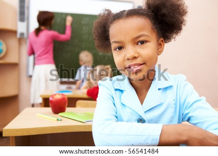 Portrait of smart schoolgirl smiling at camera during lesson in classroom - stock photo