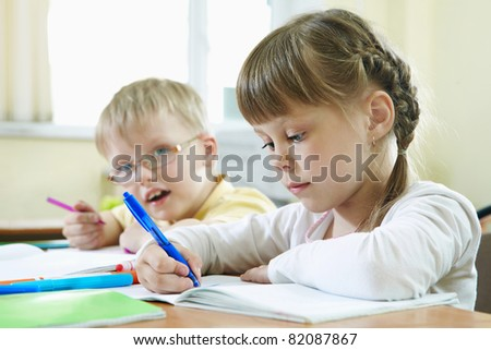 Portrait of smart schoolkids drawing at lesson in classroom - stock photo