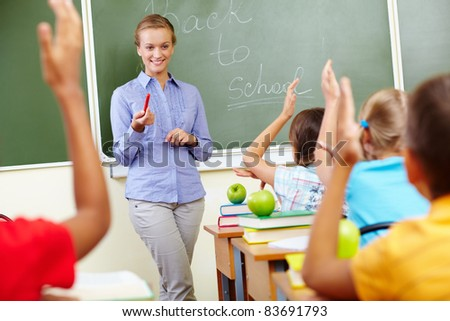Portrait of smart teacher by blackboard looking at schoolkids in classroom - stock photo