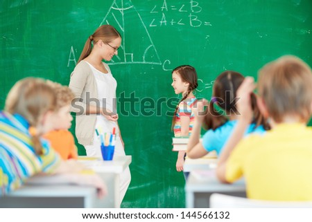Portrait of smart teacher standing by blackboard and looking at one of pupils standing near by - stock photo
