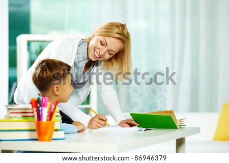 Portrait of smart tutor with pencil correcting mistakes in pupil?s notebook - stock photo