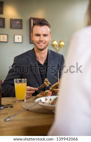 Portrait of smart young businessman having food with female colleague at cafe