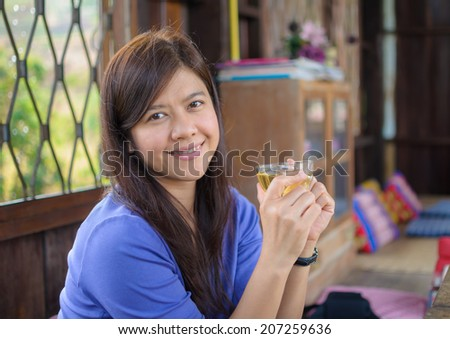 Portrait of smile asian woman having cup of tea.