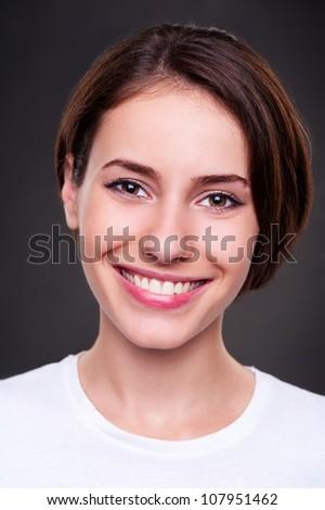 portrait of smiley cheerful woman over dark background. studio shot - stock photo