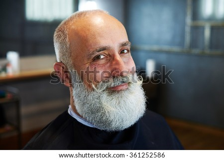 portrait of smiley stylish man with grey-haired beard and mustache in barbershop