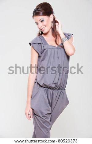 portrait of smiley stylish woman over grey background - stock photo