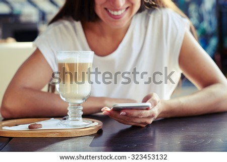 portrait of smiley young woman sitting in cafe with smartphone and cup of cappuccino - stock photo