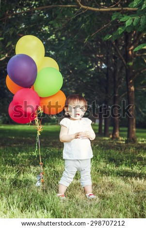Portrait of smiling adorable asian girl child, one years old, in white clothes with balloons on field meadow on sunset, concept of happy birthday holiday, toned with Instagram filters - stock photo