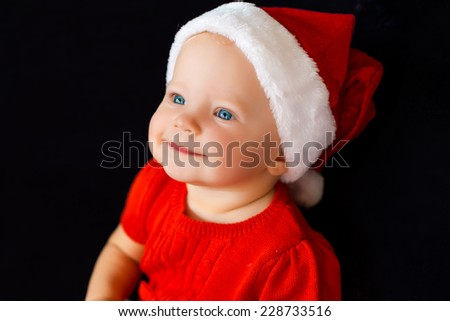 portrait of smiling adorable small baby girl in christmas hat on black background - stock photo