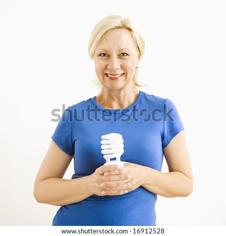 Portrait of smiling adult blonde woman holding energy-saving lightbulb. - stock photo