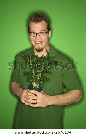 Portrait of smiling adult Caucasian man on green background holding plant. - stock photo