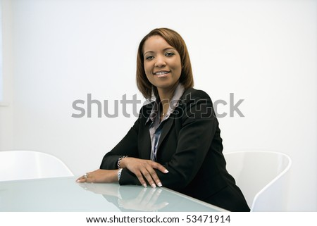 Portrait of smiling African American businesswoman sitting at office desk. - stock photo