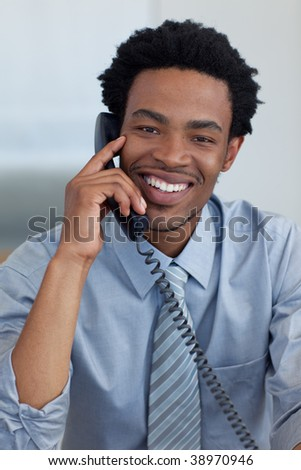 Portrait of smiling Afro-American young businessman on phone in office - stock photo