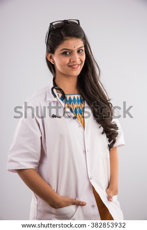 Portrait of smiling and confident female doctor with stethoscope around neck isolated over white background, indian female doctor smiling, smiling asian female doctor - stock photo