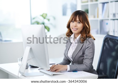 Portrait of smiling Asian business executive at her workplace