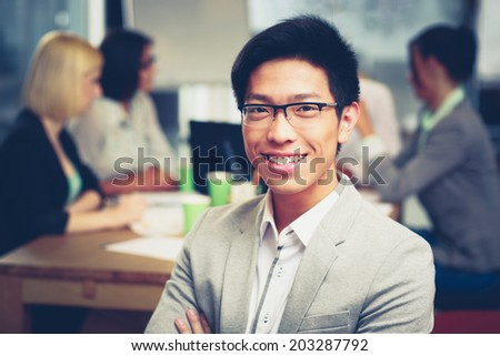 Portrait of smiling asian businessman sitting in front of colleagues - stock photo