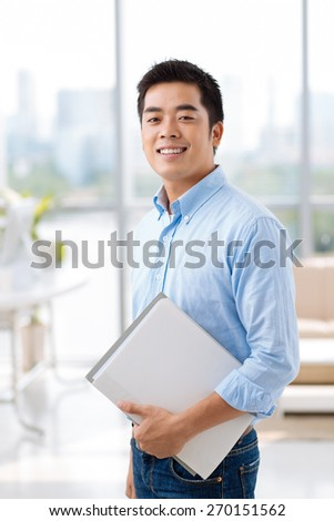 Portrait of smiling Asian man with documents smiling and looking at the camera
