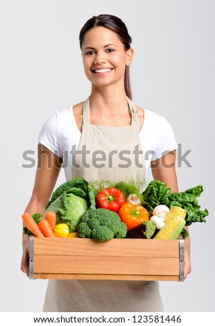 Portrait of smiling asian woman holding a crate full of fresh organic produce on grey background, promoting healthy living, diet and lifestyle - stock photo