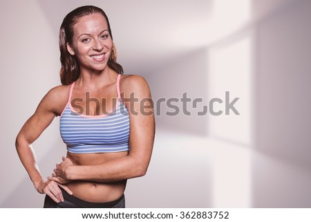 Portrait of smiling athlete with hands on hip against bright hall with windows