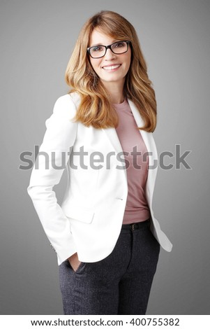 Portrait of smiling attractive businesswoman standing at isolated background.