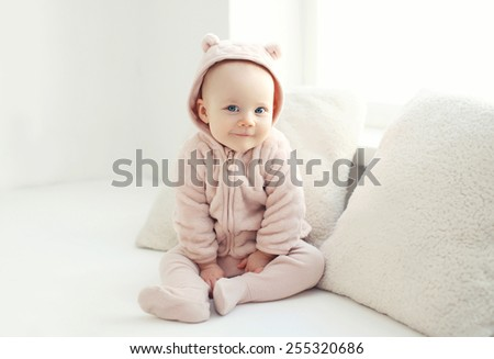 Portrait of smiling baby at home in white room - stock photo