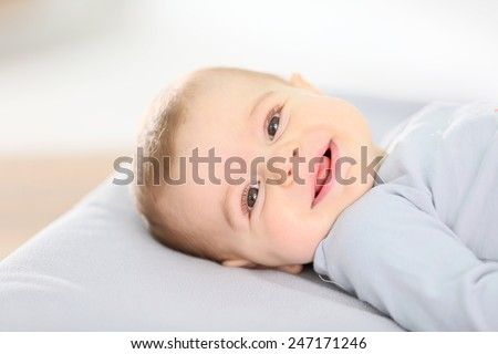 Portrait of smiling baby boy laying on changing table - stock photo