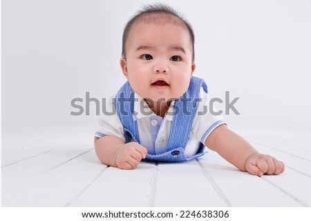 portrait of smiling baby from top on the wooden floor - stock photo