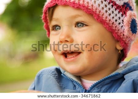 Portrait of smiling baby girl wearing woollen hat outdoors. - stock photo