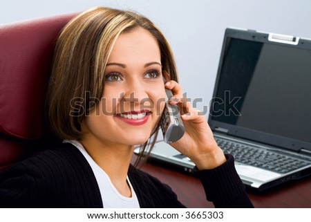 Portrait of smiling beautiful brunette businesswoman sitting on the red chair talking by her phone and opened laptop placed at the work table on the background