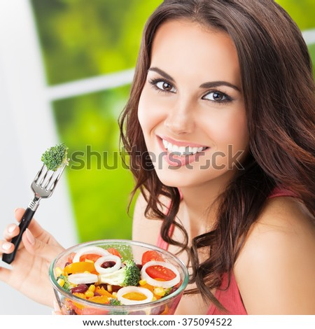 Portrait of smiling beautiful brunette woman eating salad, outdoors. Healthy eating, beauty and dieting concept. - stock photo
