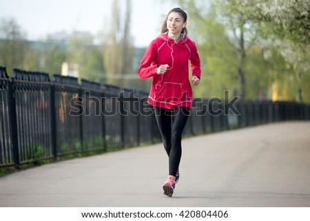 Portrait of smiling beautiful female running in park during everyday practice. Fitness woman jogging outdoors and listening music. Sport active lifestyle concept. Full length
