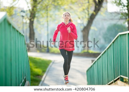 Portrait of smiling beautiful female running on the bridge during everyday practice. Fitness woman jogging outdoors and listening music. Sport active lifestyle concept. Full length - stock photo