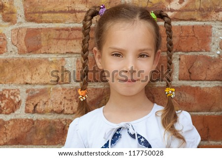 Portrait of smiling beautiful little girl close-up, against background of a brick wall.