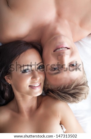 Portrait of smiling beautiful lovers posing in bed - stock photo
