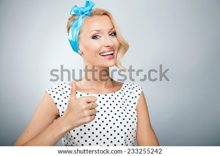 Portrait of smiling beautiful pinup woman. Girl looking at camera, showing okay. - stock photo