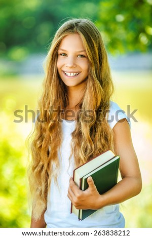 Portrait of smiling beautiful teenage girl with books, against green of summer park. - stock photo
