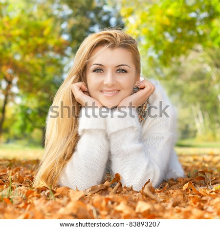 Portrait of smiling beautiful woman lying on a autumn leaves. - stock photo