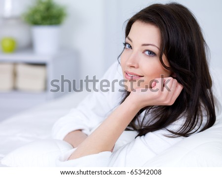 Portrait of smiling beautiful young brunette woman at home - stock photo
