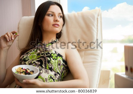 Portrait of smiling beautiful young brunette woman at home sitting near big window and eating dried fruits - stock photo