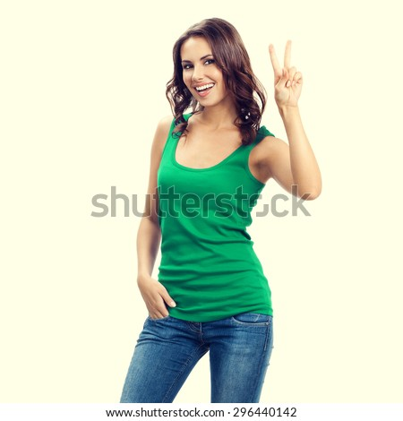 portrait of smiling beautiful young brunette woman showing two fingers or victory gesture, in smart green casual clothing - stock photo