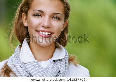 Portrait of smiling beautiful young woman, against background of autumn park. - stock photo